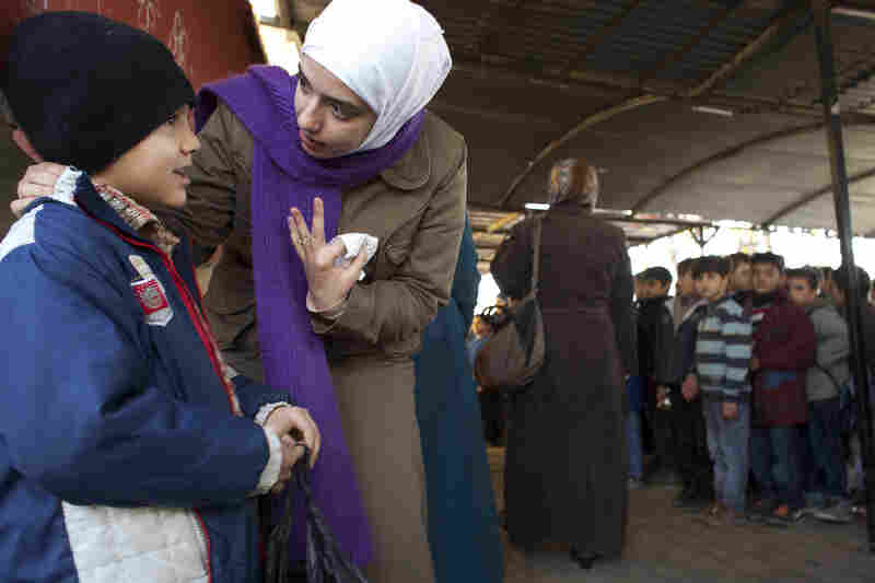 Teacher Rahaf Al Tinawie counsels a student outside class at the Albashayer School for Syrian Refugee Children. Al Tinawie says many children show signs of trauma and she sometimes meets with parents to discuss the problems the children are facing.