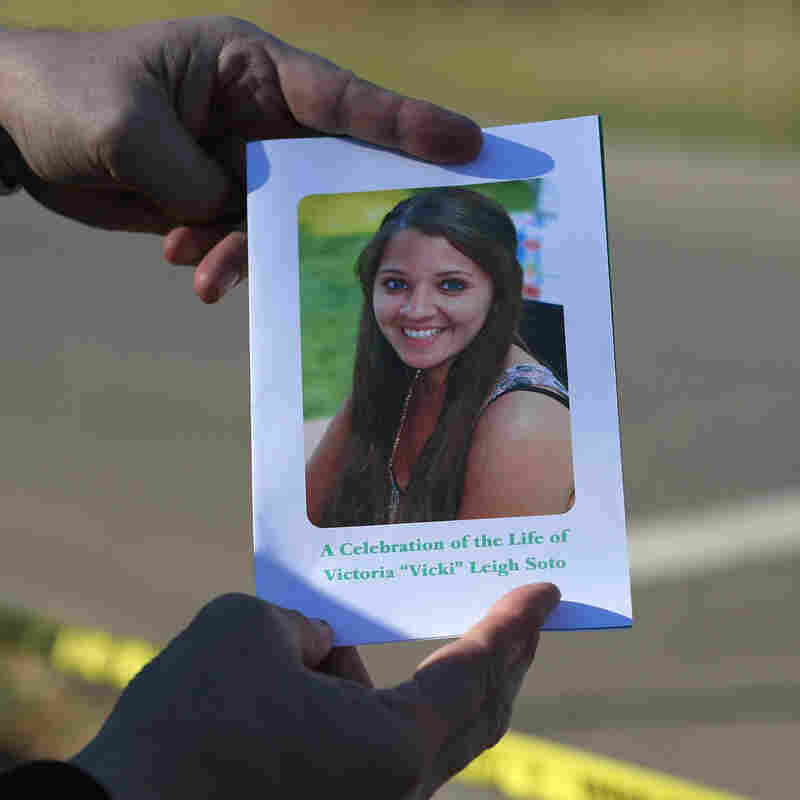 A mourner displays a program for the funeral of slain teacher Victoria Soto, 27, in Stratford, Conn.
