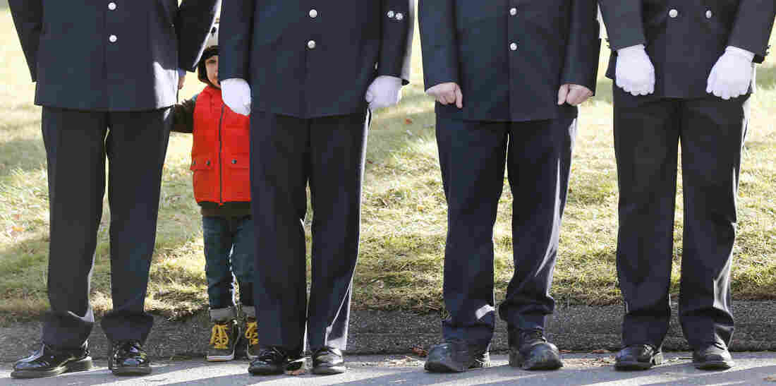A child peers through firefighters standing as the procession heads to the cemetery outside the funeral for school shooting victim Daniel Barden at St. Rose of Lima Catholic Church in Newtown, Conn.,