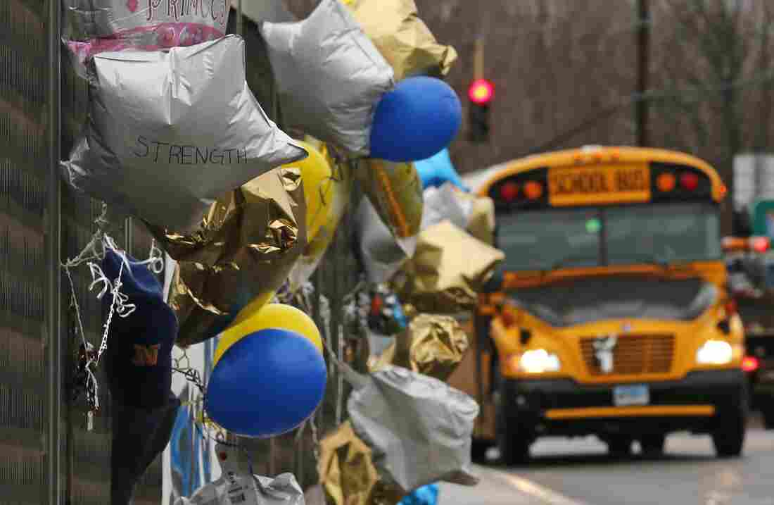 A school bus rolls towards a memorial for victims of the school shooting in Newtown, Conn., Tuesday, Dec. 18, 2012.