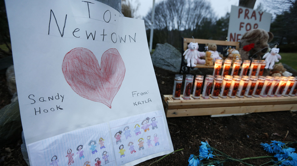 A child's message rests with a memorial for shooting victims on Sunday in Newtown, Conn. (AP)