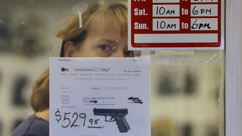 A clerk peers out from a gun shop in Seattle on Wednesday. (Elaine Thompson/AP)