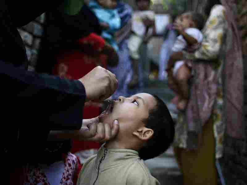 A Pakistani health worker gives a polio vaccine to a boy, while a group of women holding their children wait their turn, in an alley of a Christian neighborhood in Islamabad in October.