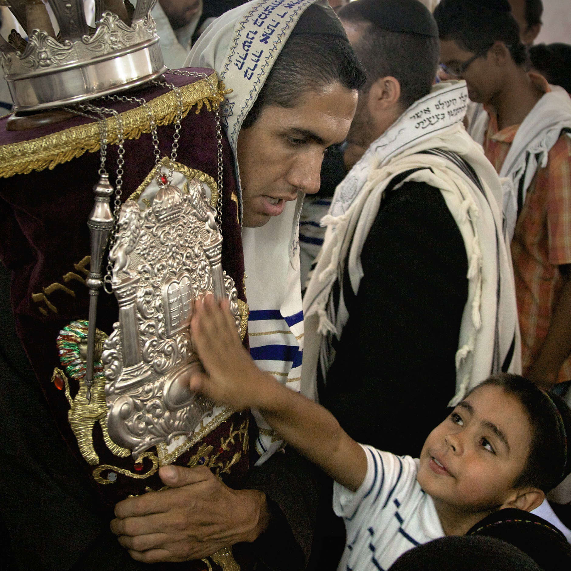 Many members of the Jewish community in Bello, Colombia, were raised as Christians. They believe their ancestors were Jews who fled the Spanish Inquisition, and so they are now Orthodox Jews. Here, a boy reaches out to the 120-year-old Torah that was written in Amsterdam and acquired by the community five years ago.