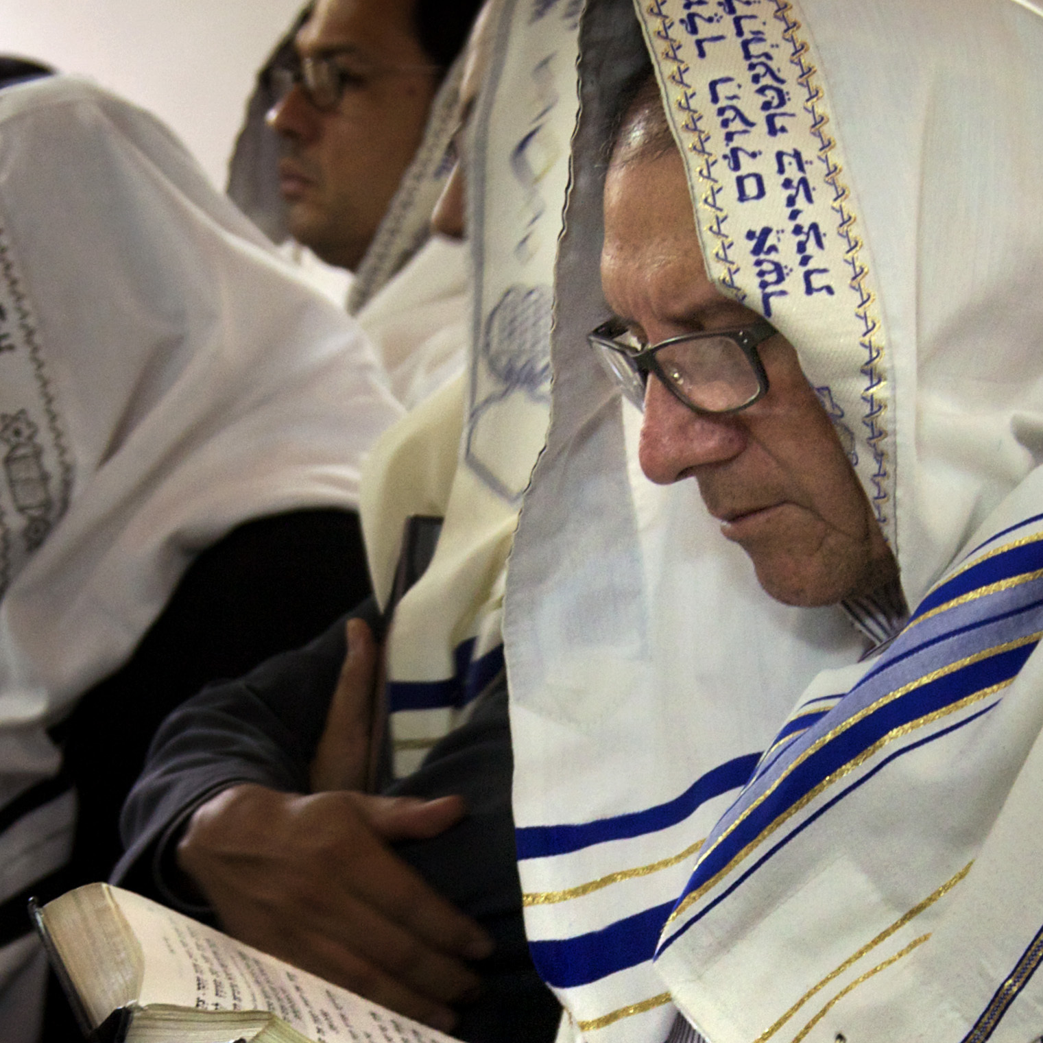 A man worships at the synagogue in Bello using a prayer book, the Siddur Birkat Shelomo, in which Spanish, Hebrew and phonetic versions are offered.