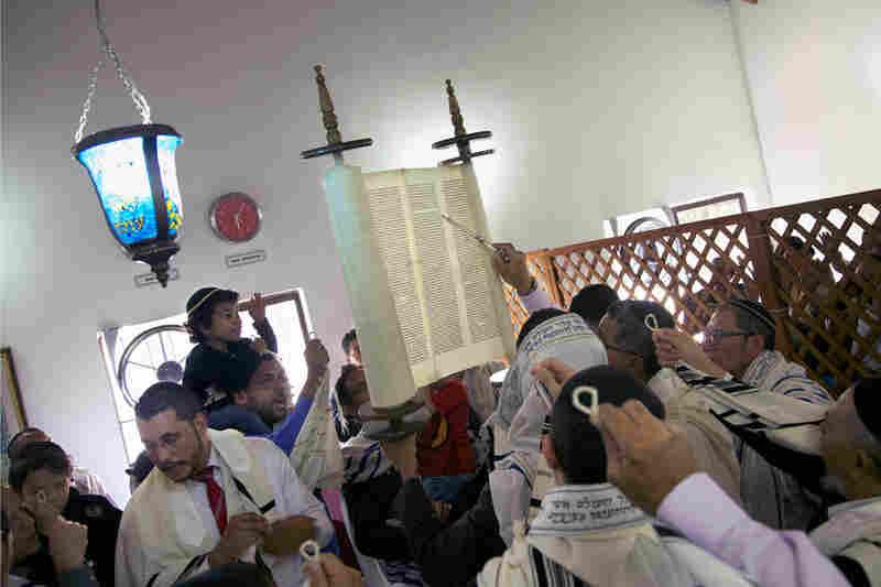 The congregation gathers around the Torah.