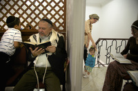 A man reads from a prayer book while a mother cares for her daughter during prayers at Bello's synagogue.