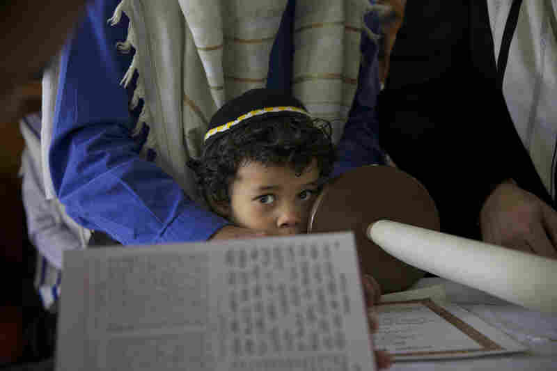 Baruj Cano, 4, watches as his father and other men from Bello's Jewish community read from the Torah.