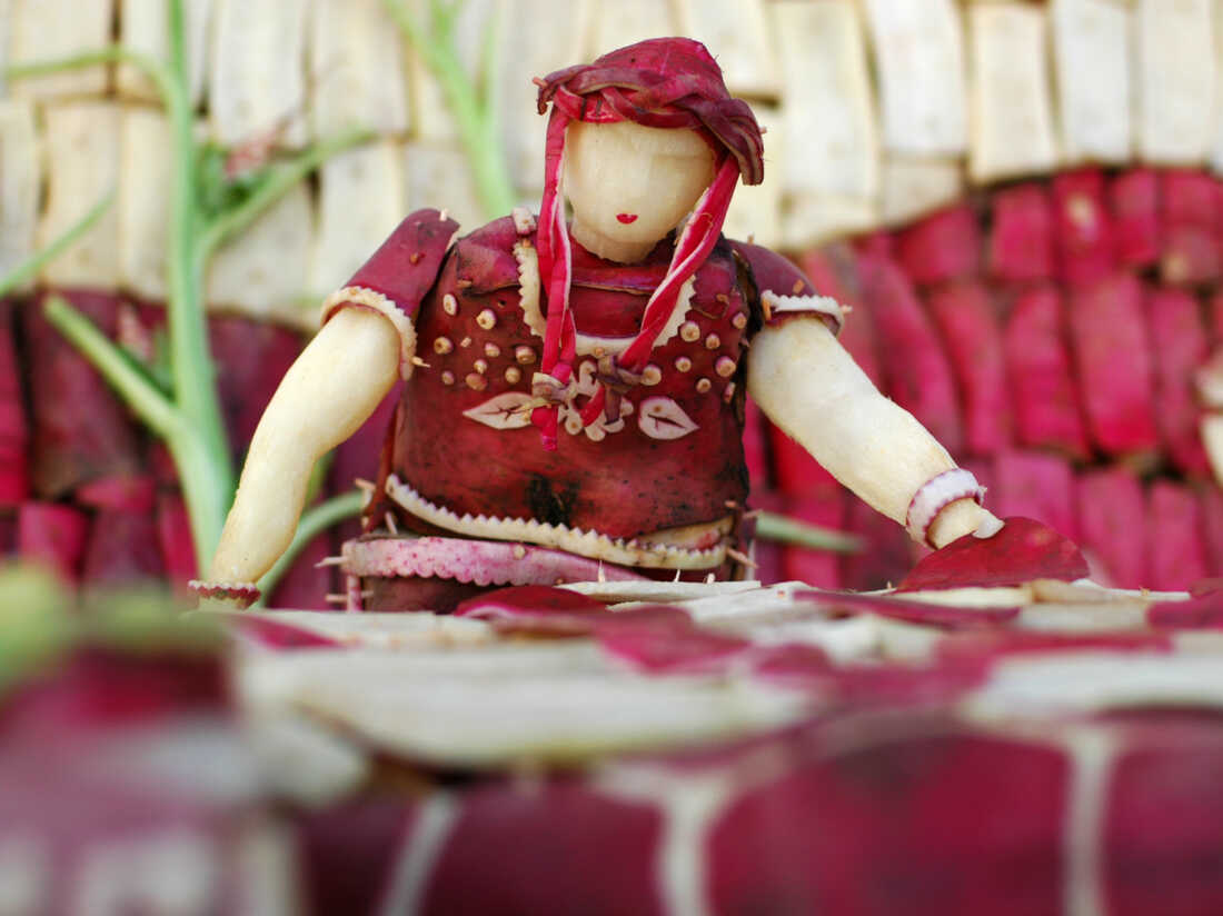 This radish woman appears to be making tortillas.