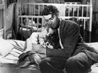 James Stewart, as George Bailey, hugs Karolyn Grimes, who plays his daughter Zuzu, in Frank Capra's It's a Wonderful Life.