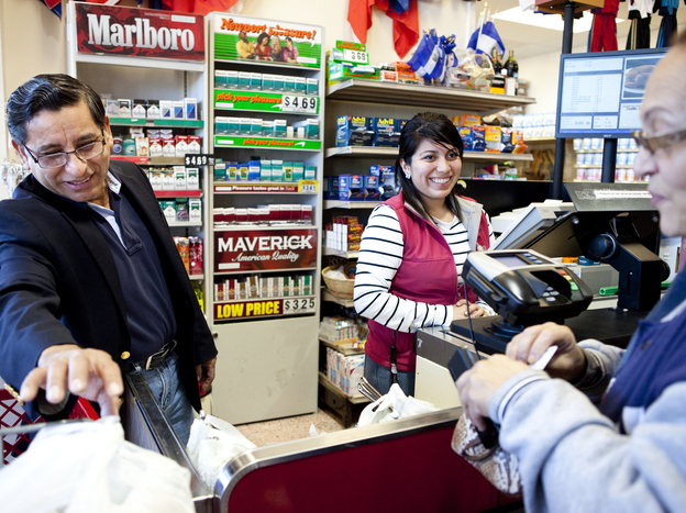 Carlos Castro, owner of Todos Supermarket in Prince William County, chats with a customer at checkout.