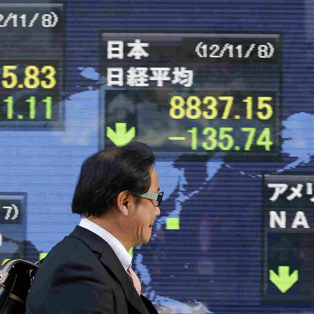 Japan's economy has been struggling for two decades and faces some of the same problems the U.S. has. Here, a man in Tokyo passes an electronic board displaying falling global markets.