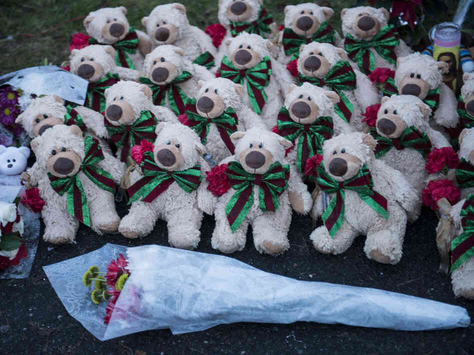 Stuffed animals and flowers at a makeshift memorial near the entrance to the grounds of Sandy Hook E