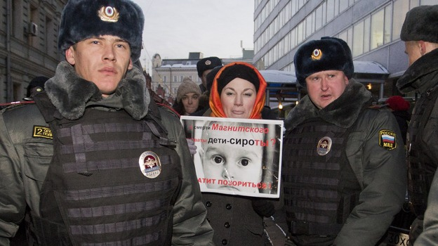 Police officers detain a protester outside the lower house of Russia's parliament on Wednesday. This week, Russian legislators passed a bill banning Americans from adopting Russian children after the U.S. passed a law that rebukes Russia for human rights abuses. (AFP/Getty Images)