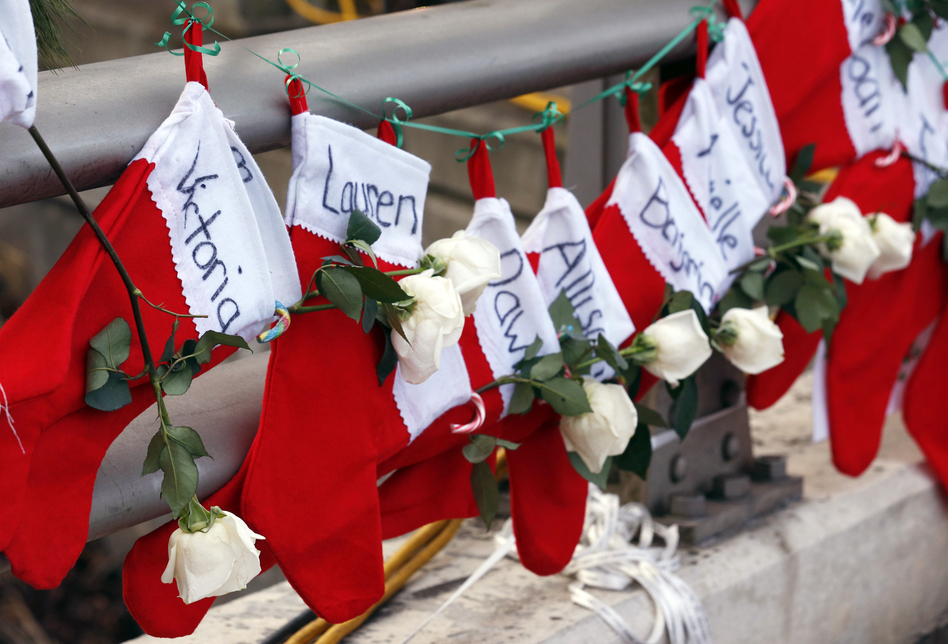 Christmas stockings with the names of shooting victims hang from a railing in the Sandy Hook village of Newtown, Conn. (Julio Cortez/AP)