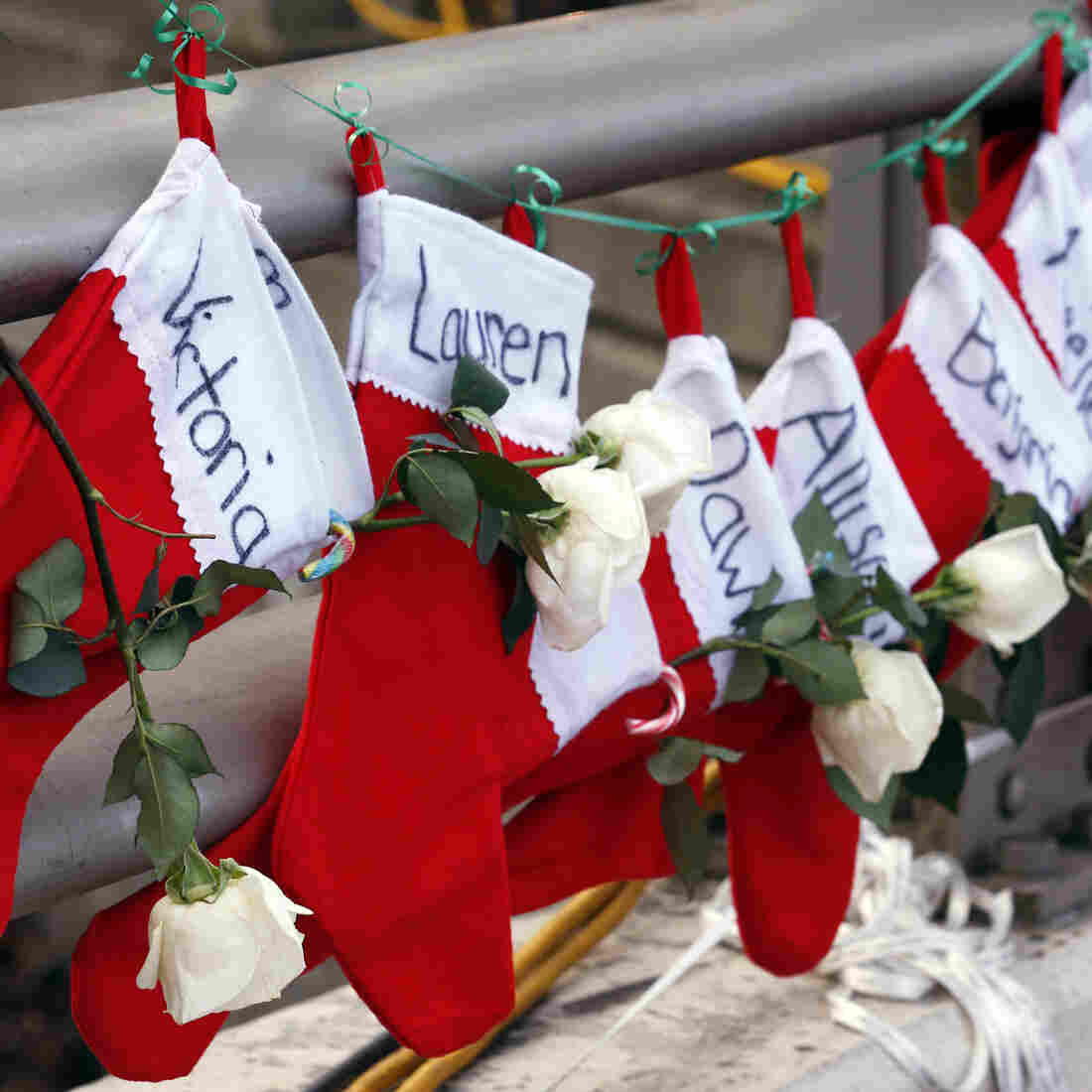 Christmas stockings with the names of shooting victims hang from a railing in the Sandy Hook village of Newtown, Conn.