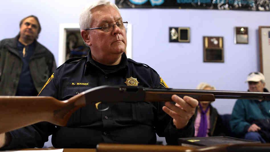 Police Lt. Ray Mesek registers a rifle at a gun buyback event on Saturday in Bridg