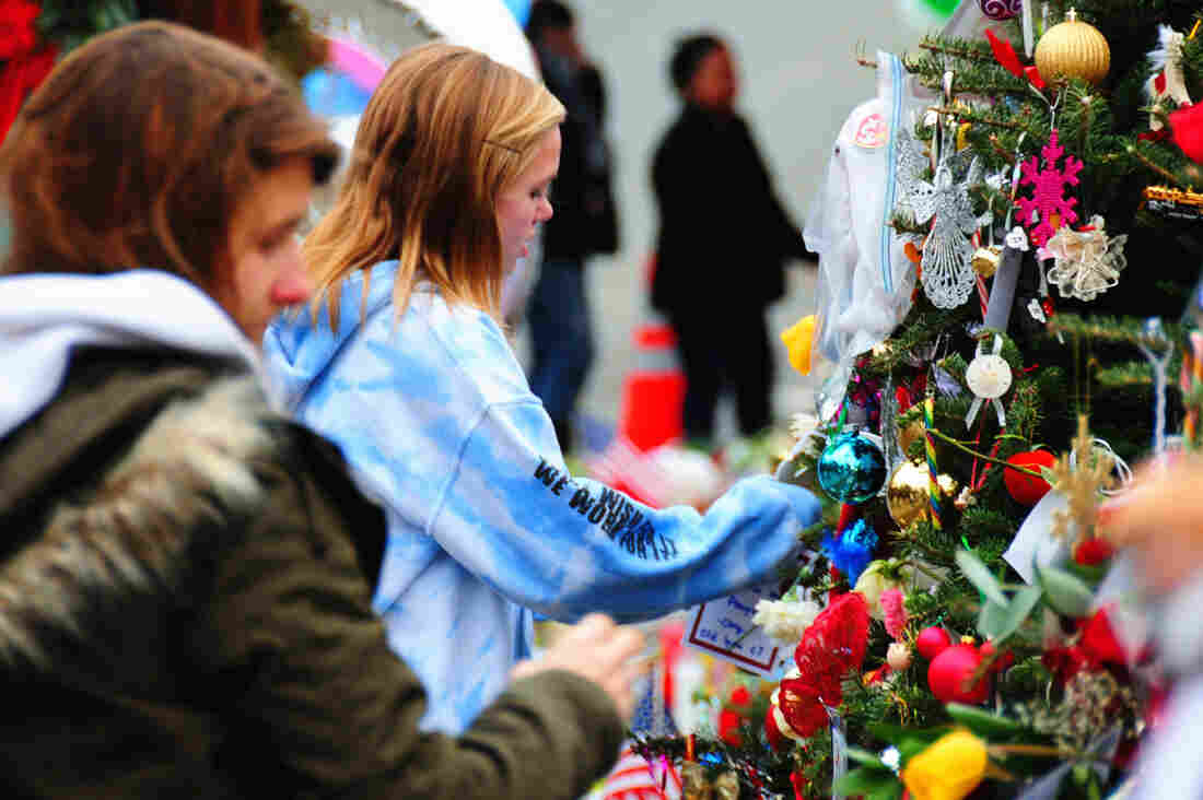 Mourners put decorations on a Christmas tree, part of a memorial in Newtown, Conn. Holiday greetings, toys and cards have flowed into the town, and some residents say the community feels closer-knit since the shooting.
