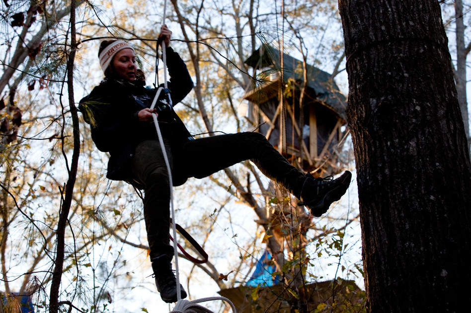 Grace Cagle, a 22-year-old protester, rappels down from the tree village. She spent a total of 17 days in the trees and was arrested once, and spent the night in jail. (NPR)