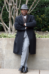 Victor Holliday, associate producer of NPR's on-air fundraising, wears a light gray wool suit (DKNY Essentials) under a black vintage overcoat with fine English stitching (Regis Rex). He considers his style