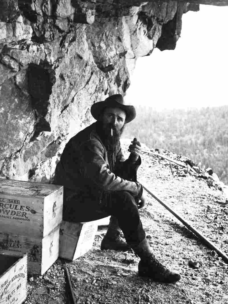 Sculptor Korczak Ziolkowski, who started the Crazy Horse memorial in 1948, smokes a cigarette near a crate of dynamite on a bluff of the Black Hills in 1950.