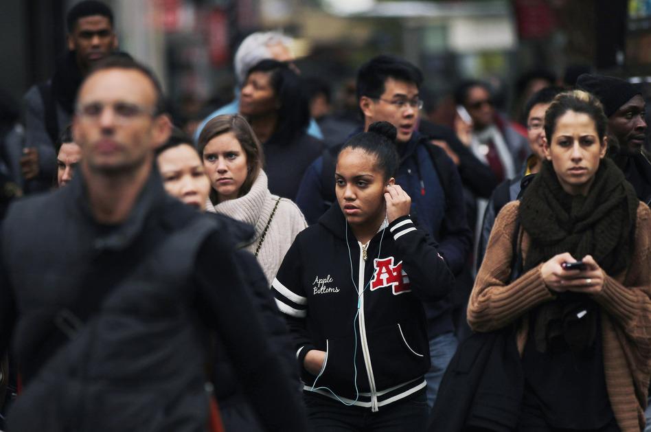 A crowd crosses the street in midtown Manhattan.