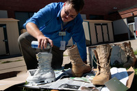 David Easterling, manager of the Suicide Prevention Program at Fort Riley in Kansas spray-paints Army boots white in 2009 as part of an on-base display to commemorate the six Fort Riley soldiers who committed suicide in 2008.