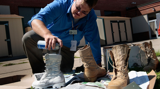 David Easterling, manager of the Suicide Prevention Program at Fort Riley in Kansas spray-paints Army boots white in 2009 as part of an on-base display to commemorate the six Fort Riley soldiers who committed suicide in 2008. (Getty Images)