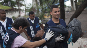 "A suspected crack user is voluntarily removed from a local ""Crackland"" and carried by a social worker to a waiting van that will take her to a nearby shelter in Rio de Janeiro in November."