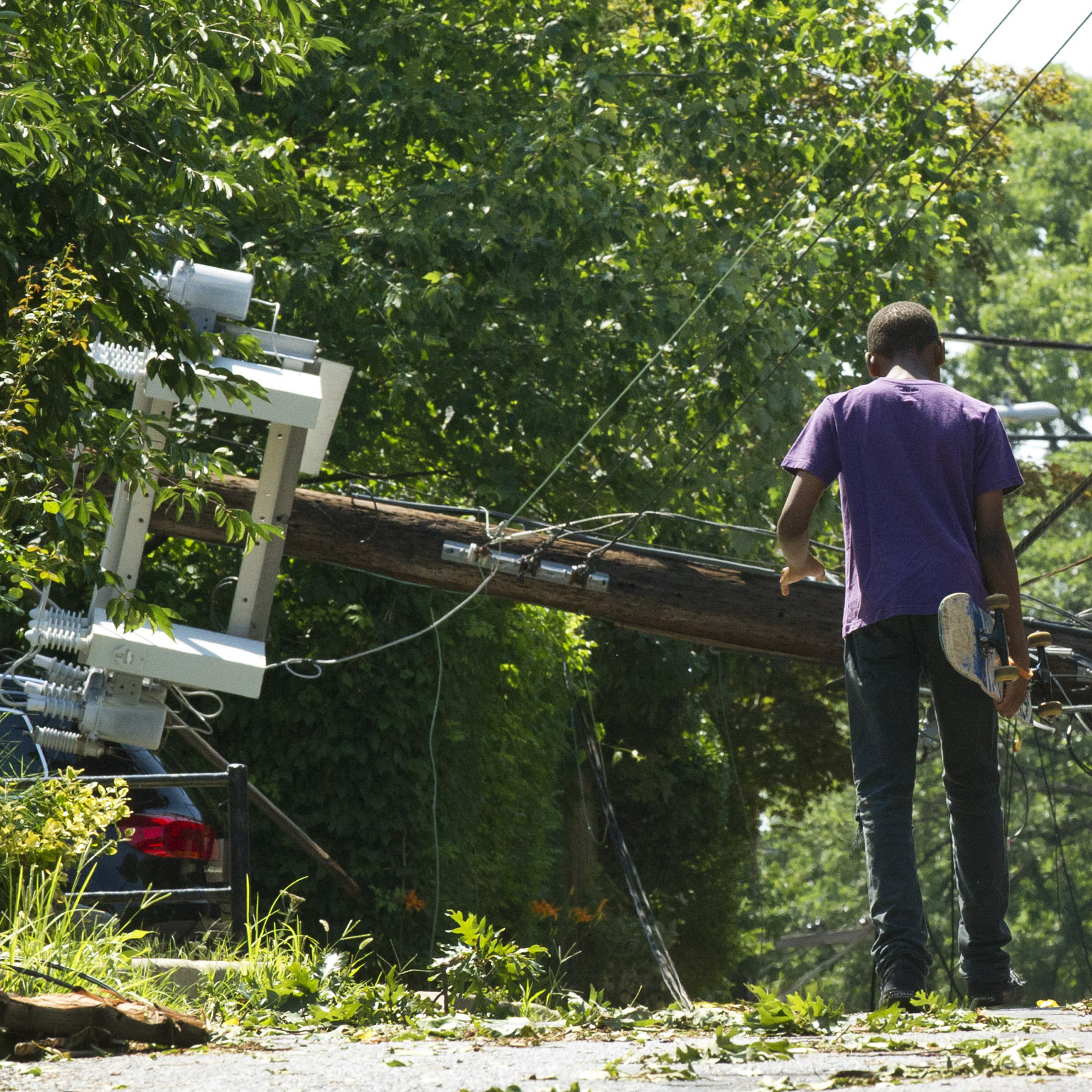 People in Takoma Park, Md., walk toward a fallen telephone pole on June 30 after heavy overnight thunderstorms devastated the Washington, D.C., metropolitan area. The line of storms known as a derecho left over 1 million people without power.