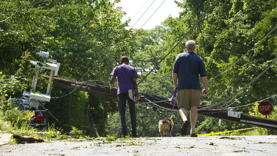 People in Takoma Park, Md., walk toward a fallen telephone pole on June 30 after heavy overnight thunderstorms devastated the Washington, D.C., metropolitan area. The line of storms known as a derecho left over 1 million people without power. (UPI/Landov)