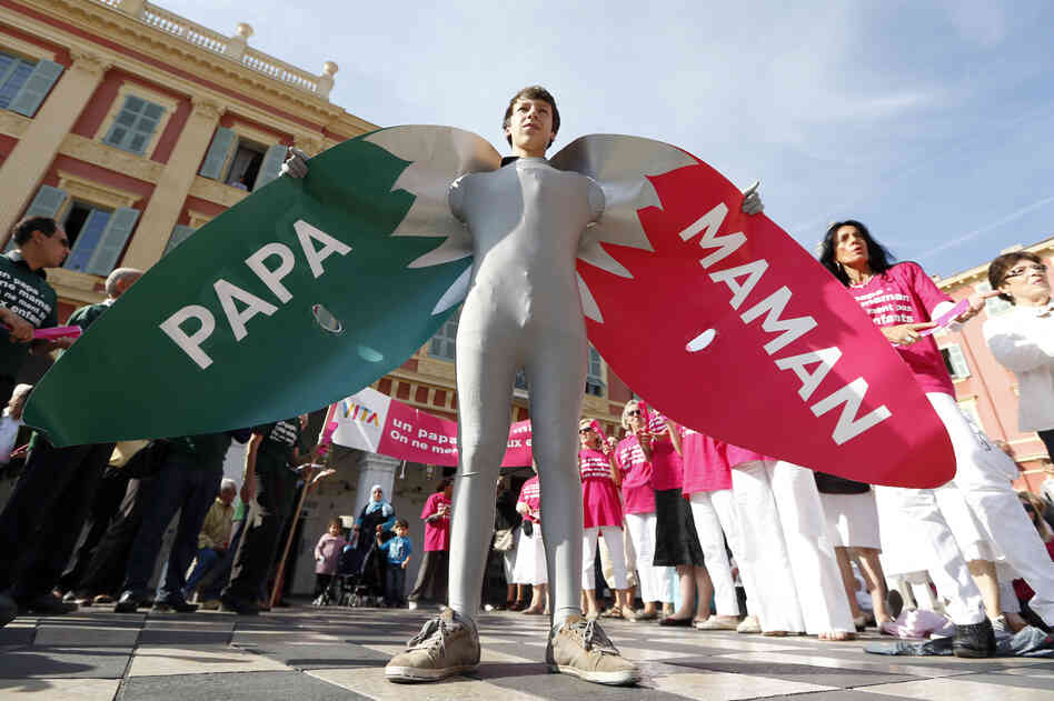 "A man wears a costume reading ""Dad"" and ""Mom"" during a demonstration against gay marriage and ado"