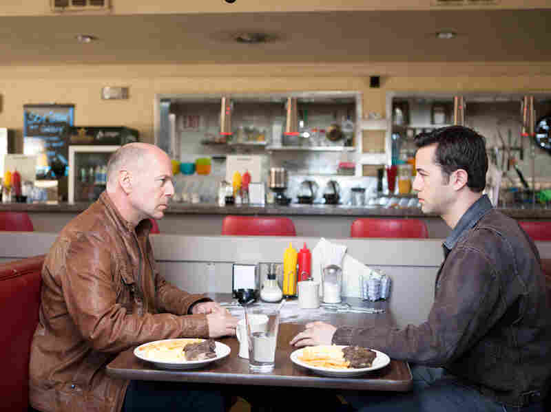 Young Joe (Joseph Gordon-Levitt) and Old Joe, the same man at two different moments of his life, stare each other down.
