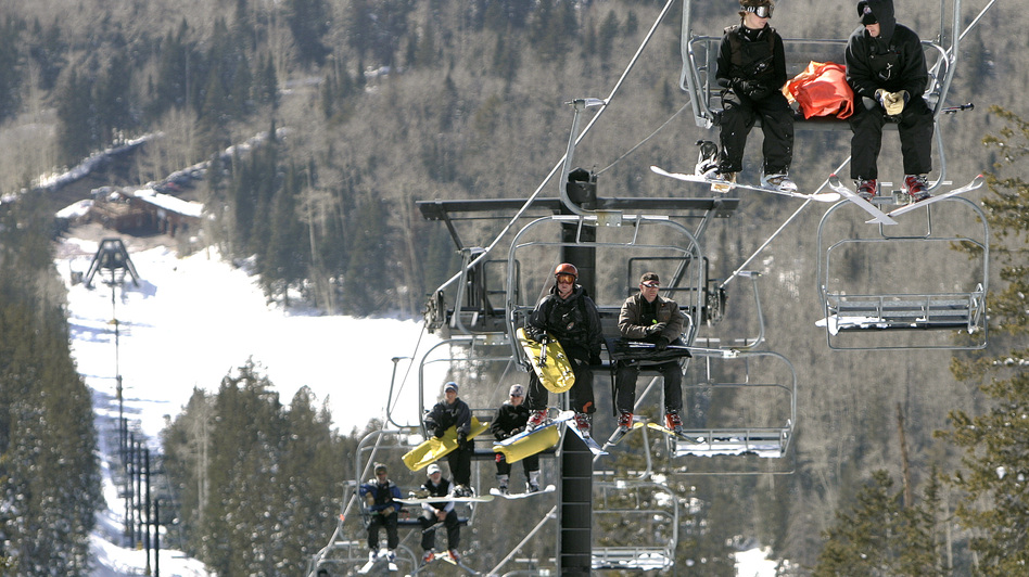 The Arizona Snowbowl resort began making snow exclusively with reclaimed wastewater this week. In this file photo, employees go up a ski lift at the resort. (AP)