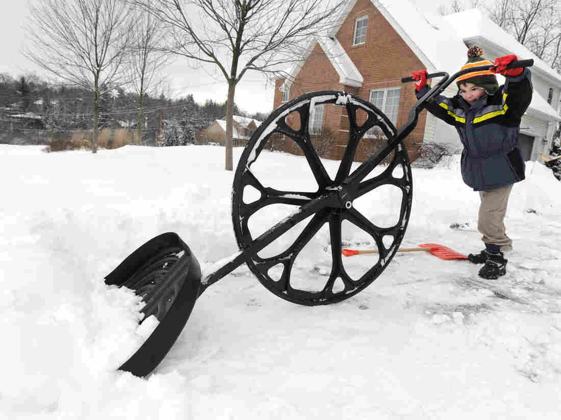 "Nathan Lee, 5, was using a ""wovel"" to move snow from his family's driveway earlier today in State College Pa."