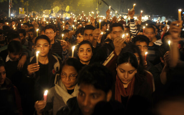 Protesters hold candles during a rally in New Delhi late Saturday following the death of a woman gang-raped on a bus.