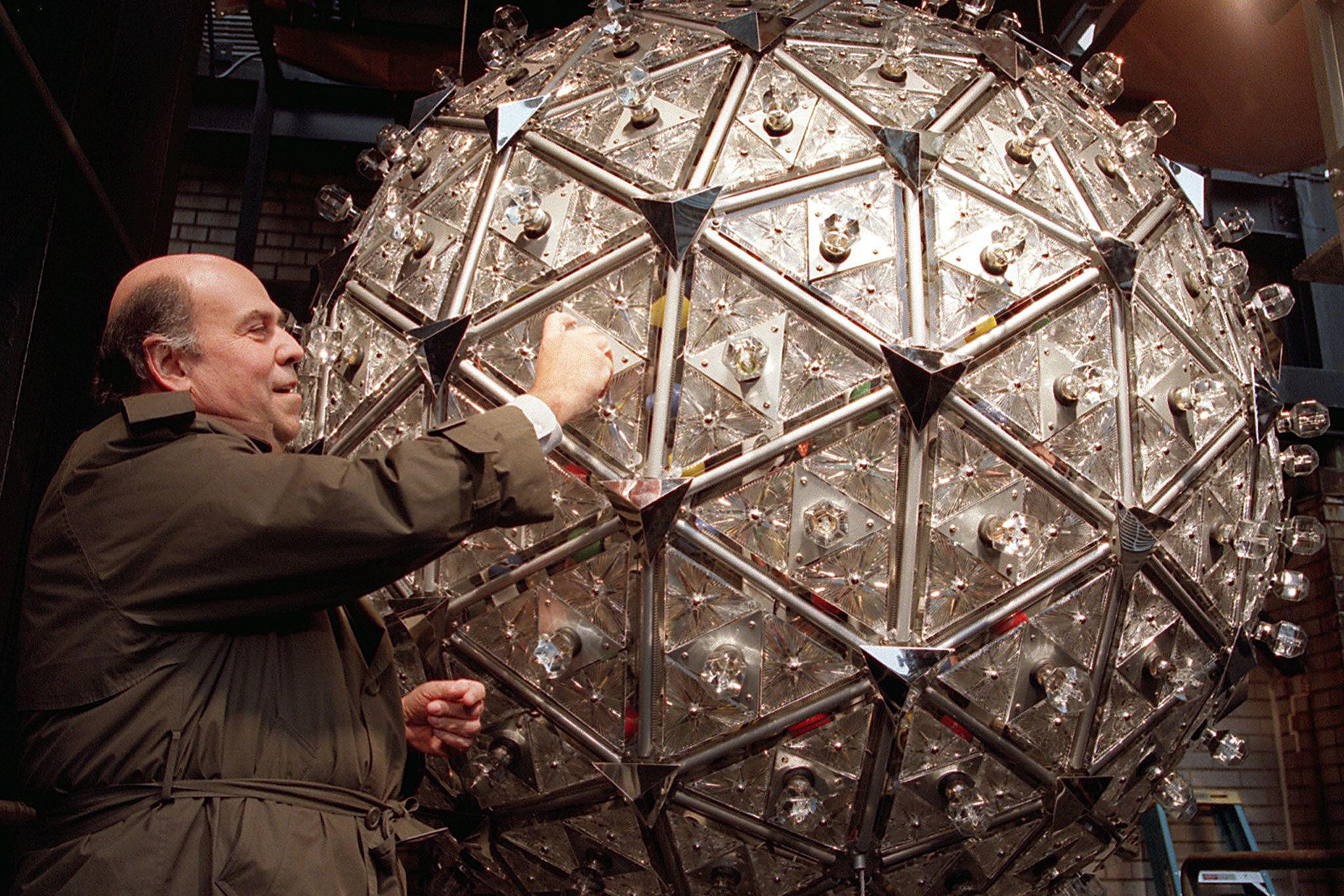 Steven Goldmacher of Philips Lighting Co. screws in a light bulb, Dec. 20, 1999. The 1,070-pound crystal ball, 6 feet in diameter, made its debut at the millennial celebration.