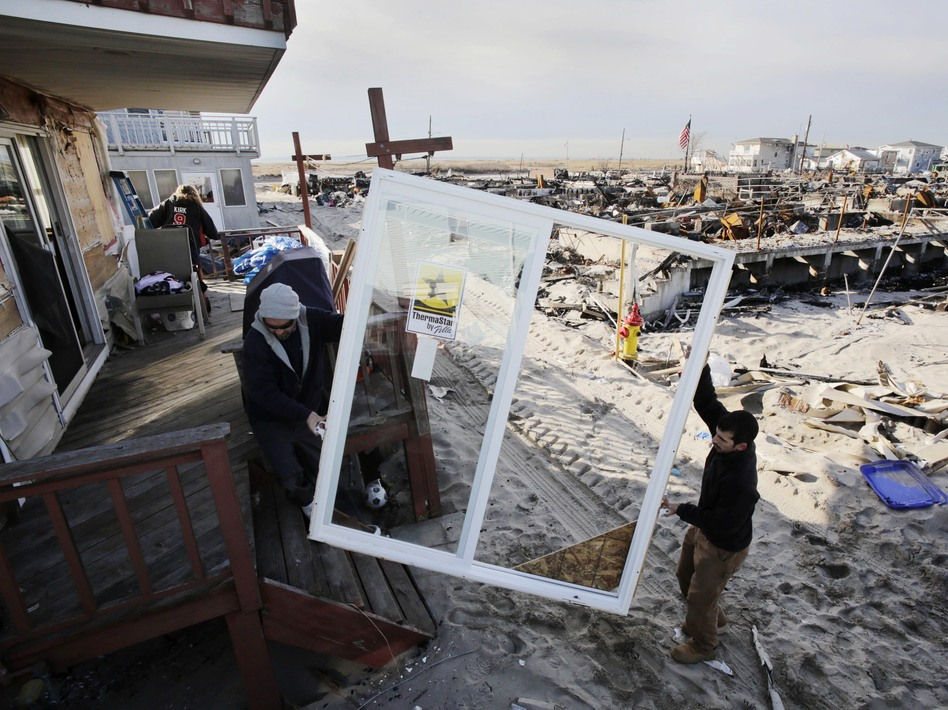 Contractors Benny Corrazo, left, and Michael Bonade install a new set of sliding glass doors in a home that survived Superstorm Sandy in the Breezy Point section of New York on Dec. 20, 2012. Some economists say that reconstruction efforts may stimulate the economy.