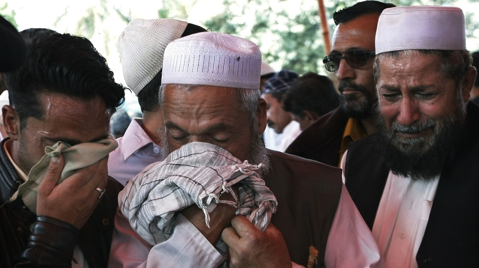 Men mourn over the deaths of their family members during their funeral procession in Karachi, Pakistan last week. Police said gunmen have wounded a prominent Sunni cleric and killed his guards and his driver in an apparently sectarian attack in southern Pakistan. (AP)