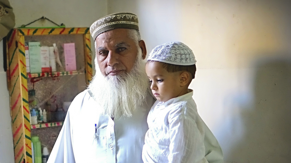 Gul Mohammed Khan has lost three sons in sectarian violence during the last two years, in Karachi, Pakistan. He stands here with some of his grandchildren who have lost their fathers. When he looks at his grandchildren, he says, he sees his sons. (Dina Temple-Raston/NPR)
