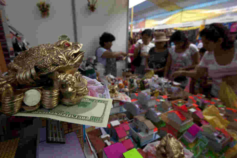 Fake money and coins along with small-scale homes are displayed at the Market of Wishes in Lima, Peru. As part of their New Year's traditions, Peruvians buy miniature representations of the things they desire to acquire in the coming year.