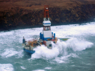 Waves crash over the Kulluk oil rig, which washed aground on Sitkalidak Island, Alaska. Officials say aircraft have not spotted any signs of a fuel leak from the rig, which reportedly does not contain crude oil.