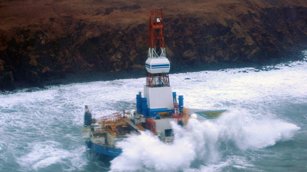 Waves crash over the Kulluk oil rig, which washed aground on Sitkalidak Island, Alaska. Officials say aircraft have not spotted any signs of a fuel leak from the rig, which reportedly does not contain crude oil. (Coast Guard)