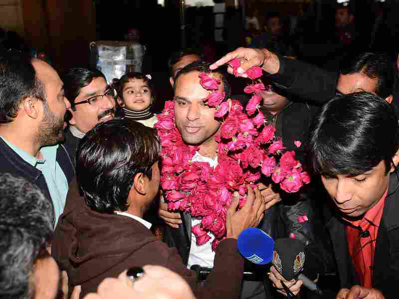 """Pakistanis welcome Muhammad Shahid Nazir, center, the singer of """"One Pound Fish,"""" at Lahore's airport Thursday."""