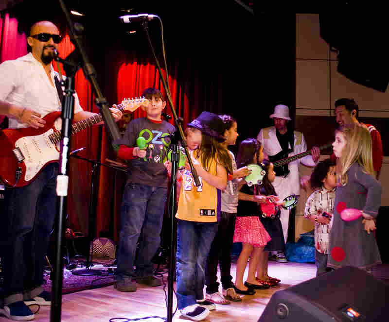 Ozomatli invites kids onstage for a performance.