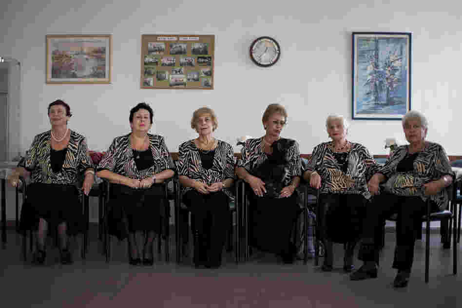 A choir practices in a government-funded elderly care facility catering to Russian-speaking immigrants in Ashdod. The choir sings Russian standards and Israeli folk songs translated into Russian.