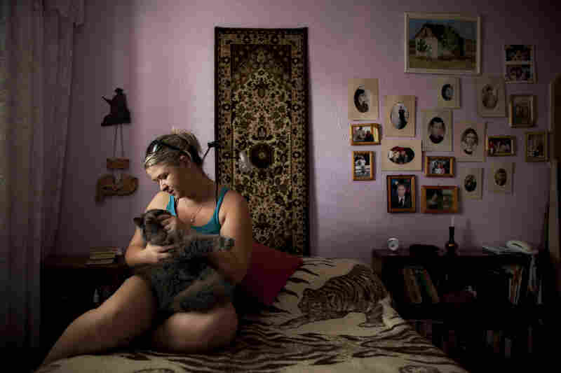 Alexandra Bahman, who immigrated to Israel from Moldova in 2006, sits in her bedroom with her cat in Ashdod. Bahman left Moldova with the carpet and photos that now decorate her bedroom walls.
