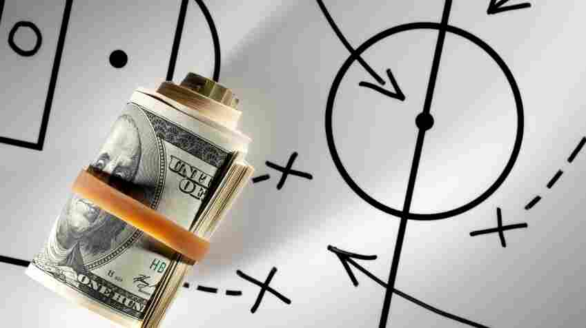 Roll of dollars on a blackboard with football strategy planning.