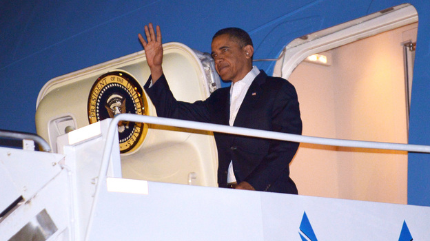 President Barack Obama  steps off Air Force One at Hickam Air Force Base near Honolulu, Hawaii, Wednesday. Obama returned to Hawaii to continue his vacation — prompting questions about how he will sign the fiscal cliff bill. (AFP/Getty Images)