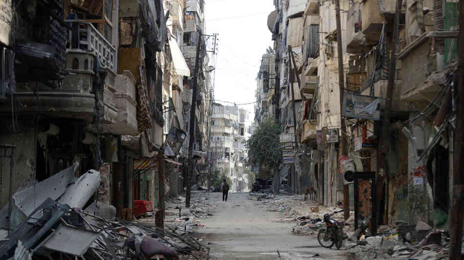 An almost deserted, rubble-filled street in Aleppo,